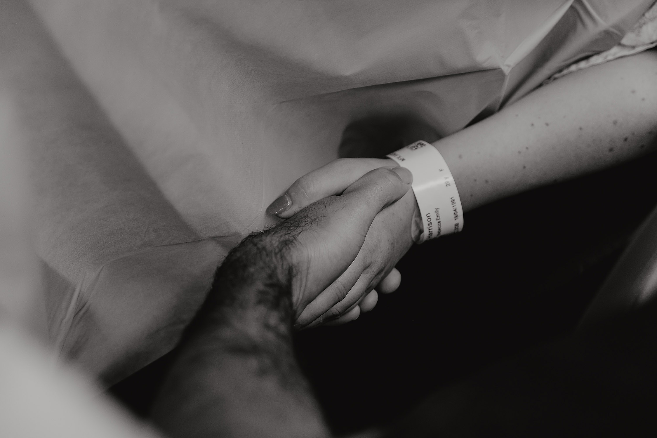 partner holding womans hand labour birth photographer christchurch