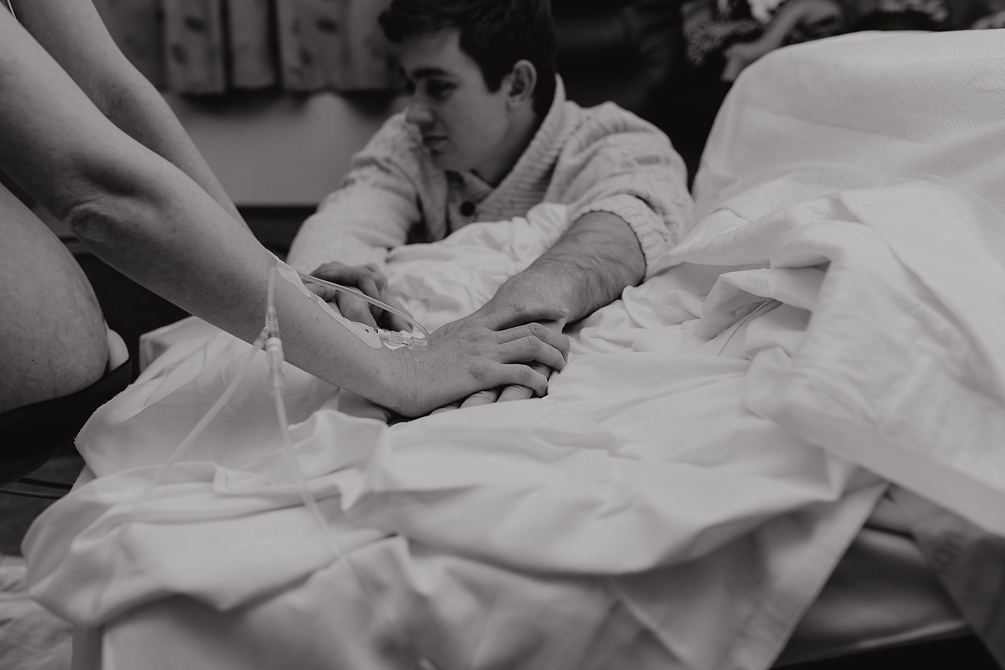 mum and dad holding hands during birth Christchurch Birth Photographer
