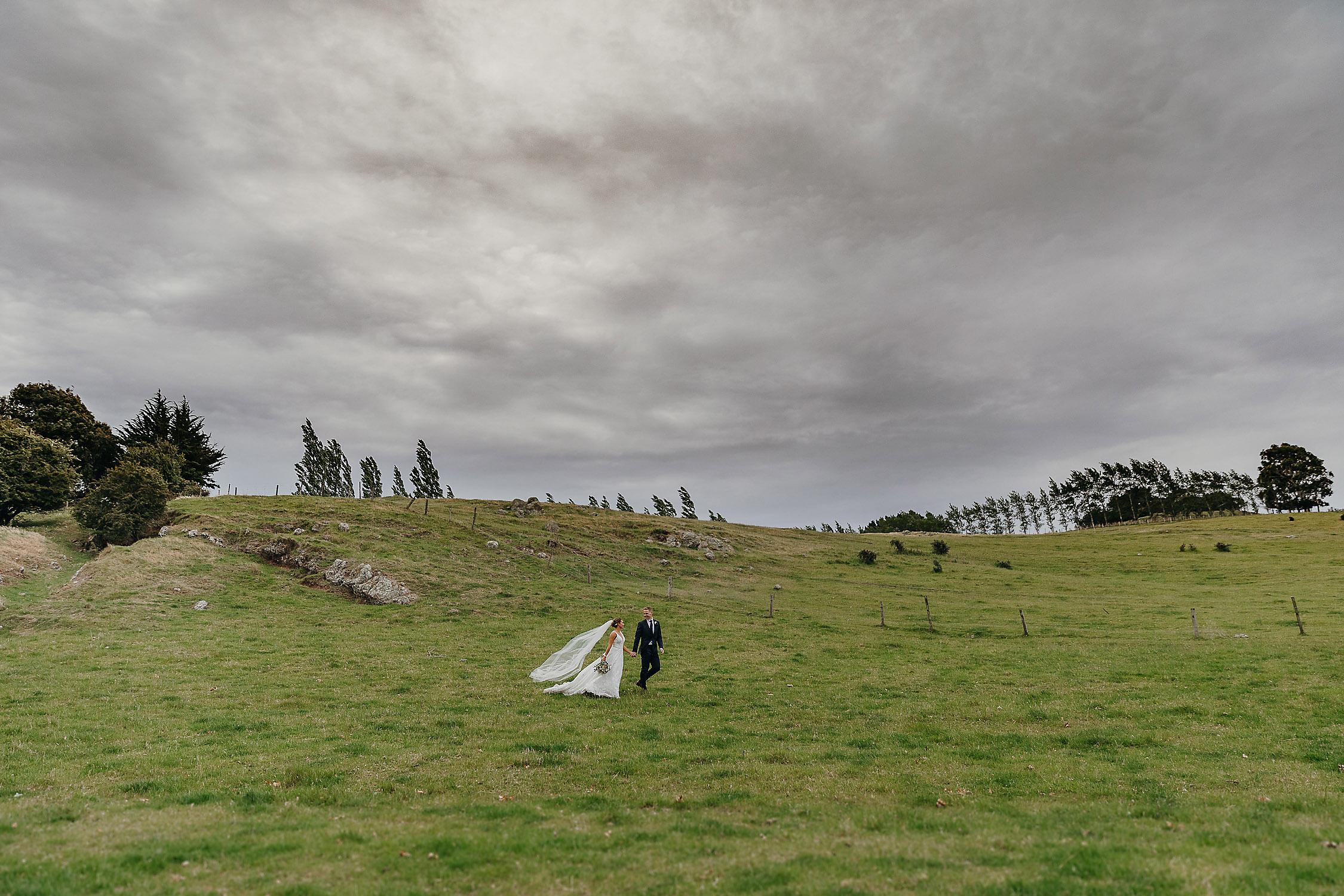 bride and groom walking on green hills wedding photographer christchurch