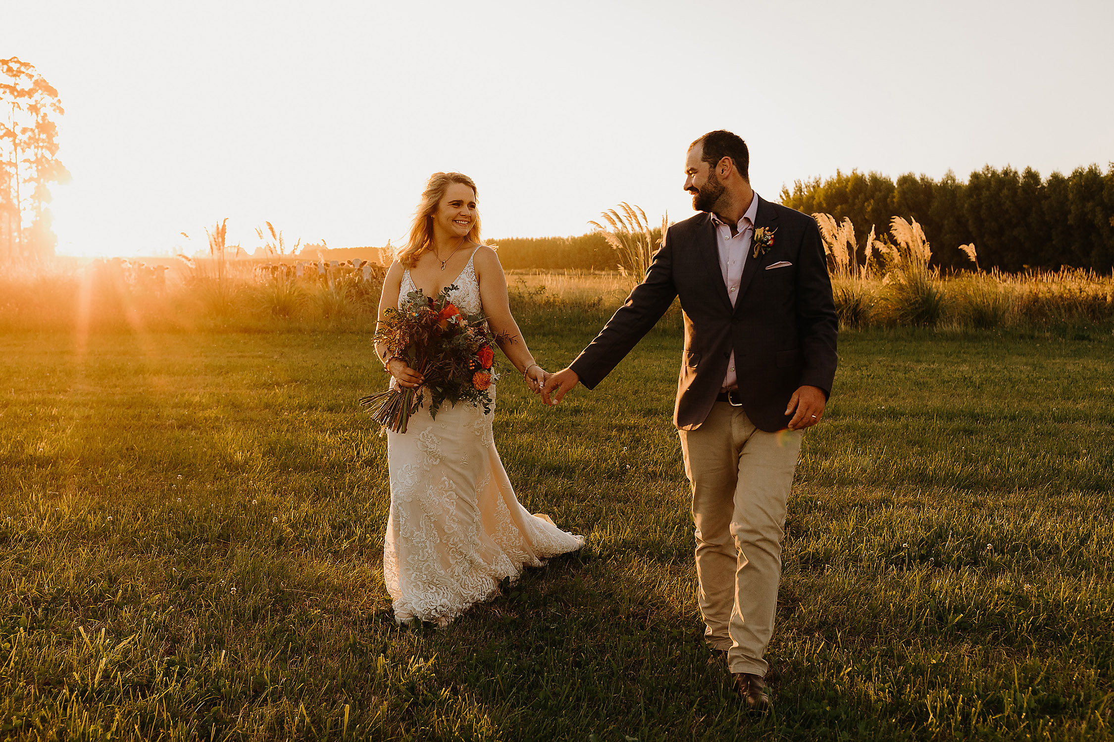 bride and groom walking at sunset rural paddock wedding photographer christchurch