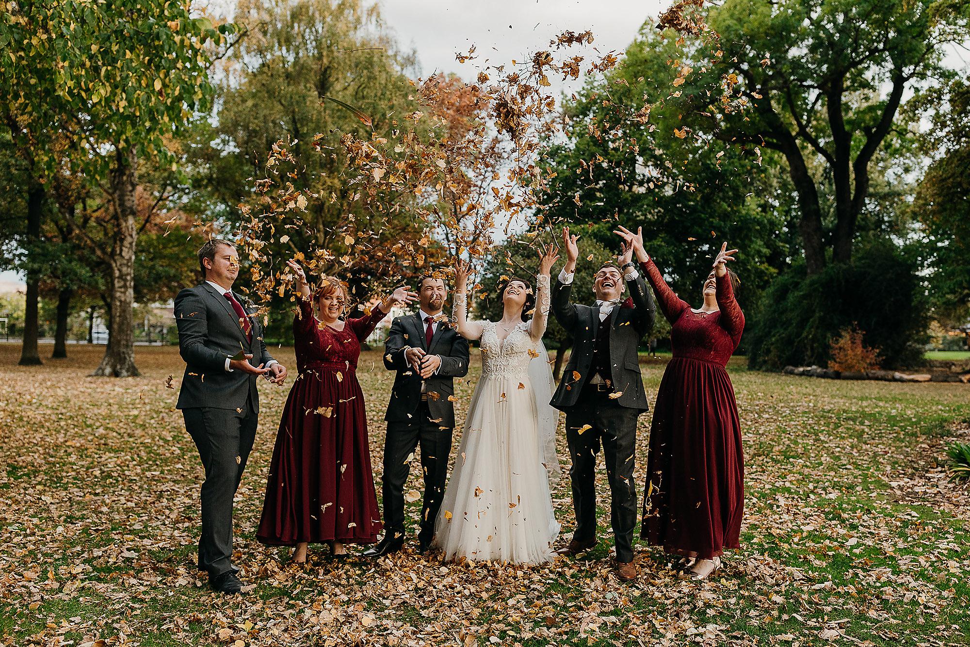 bridal party throwing leaves autumn wedding riccarton house christchurch wedding photographer