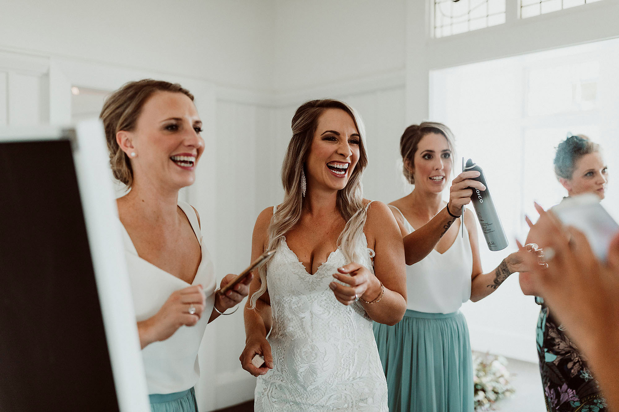 bride getting ready laughing with bridesmaids christchurch wedding photographer