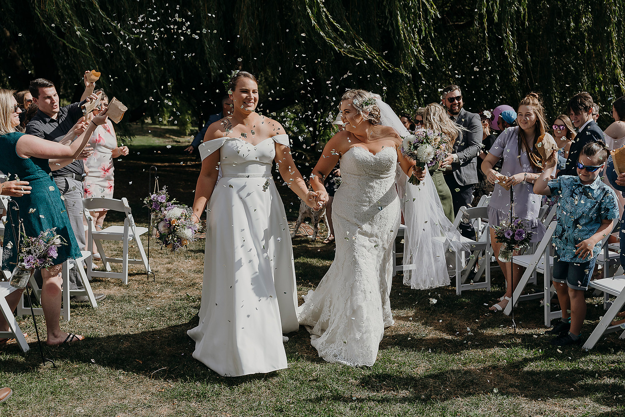 bride and bride walking down aisle with petals confetti just married lesbian wedding christchurch wedding photographer