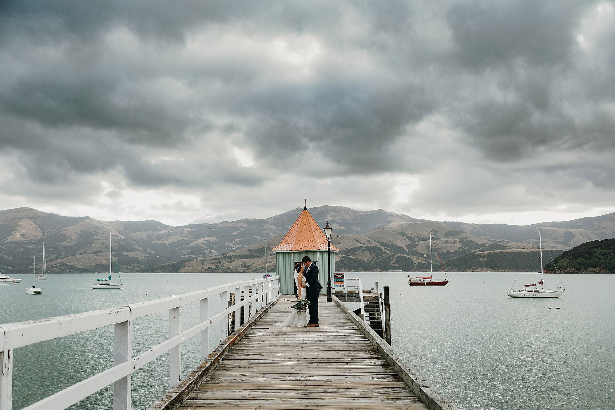bride and groom standing on wharf at akaroa christchurch wedding photographer