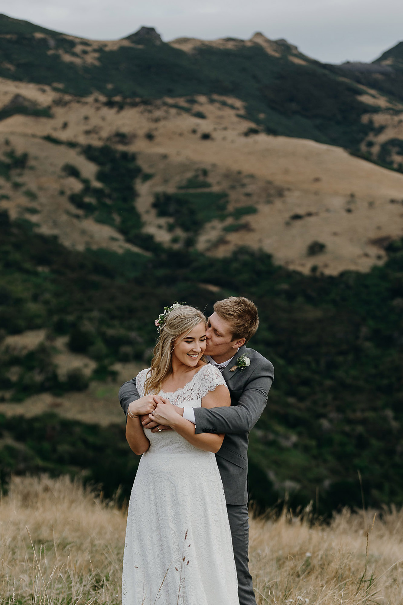 bride and groom cuddling together in the hills at Akaroa christchurch wedding photographer