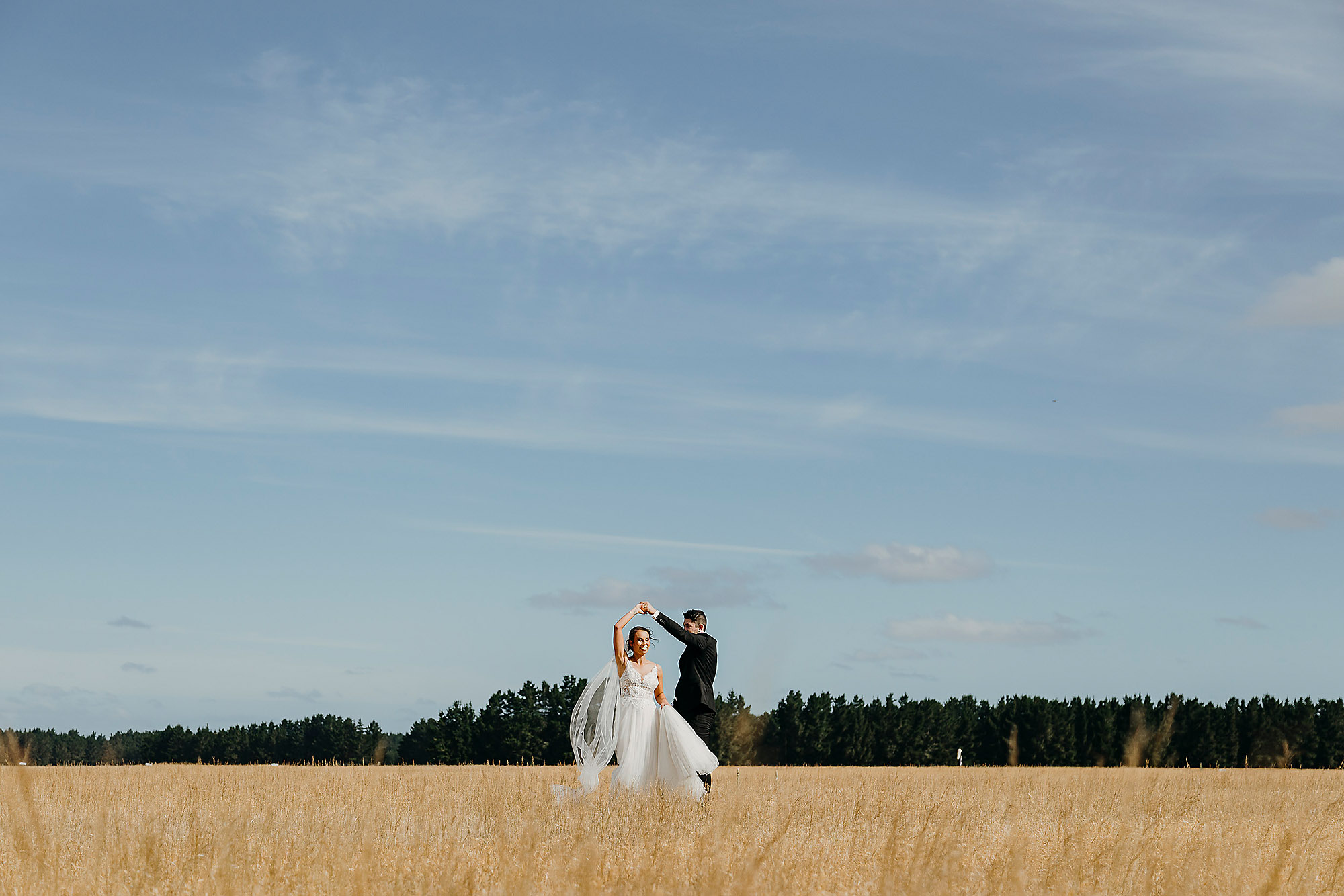 Christchurch Wedding Photographer wedding photo of bride and groom dancing in field at West Melton Christchurch Rebecca Claridge Photography