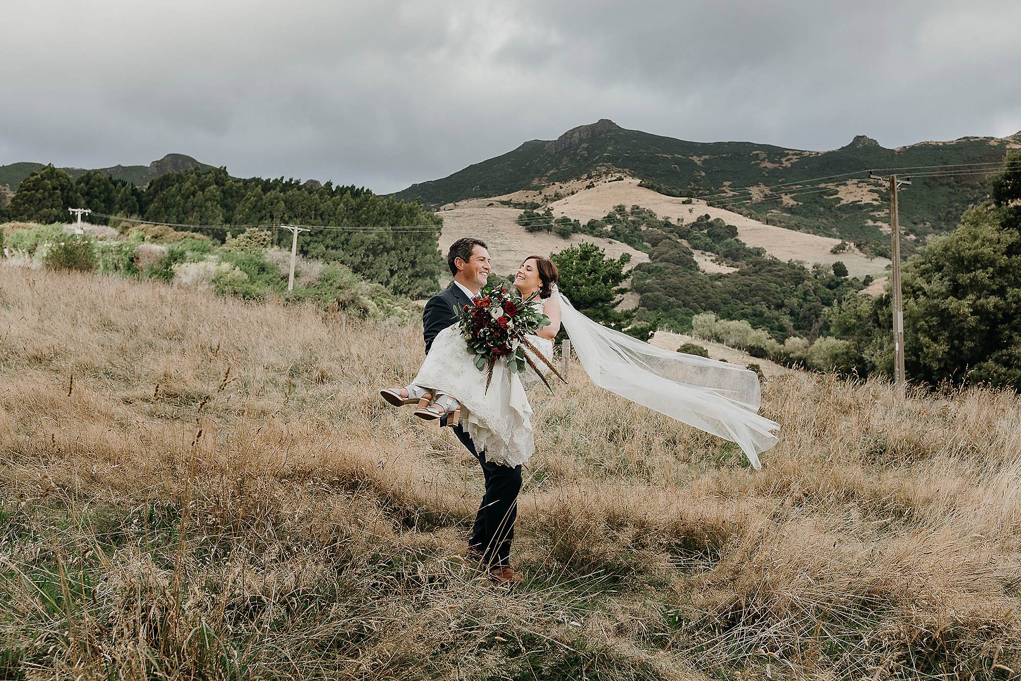Christchurch Wedding Photographer groom carrying bride in wedding photo at Mt Vernon Lodge Akaroa Rebecca Claridge Photography
