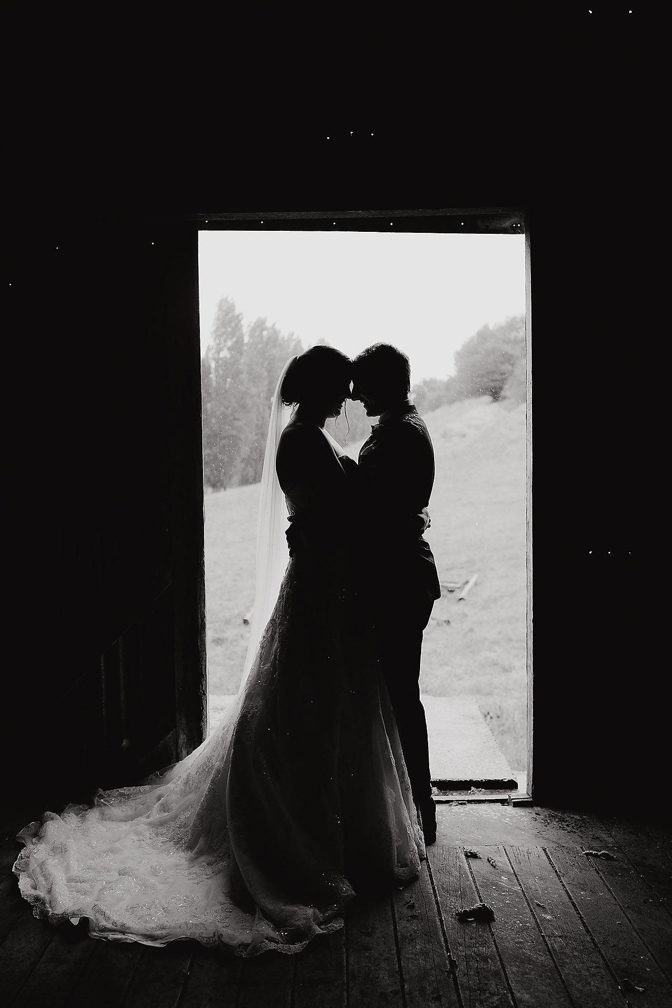 bride and groom silhouette in wool shed rossendale vineyard black and white bride and groom kissing at sunset ontop of hills silhouette jonkers farm christchurch wedding photographer