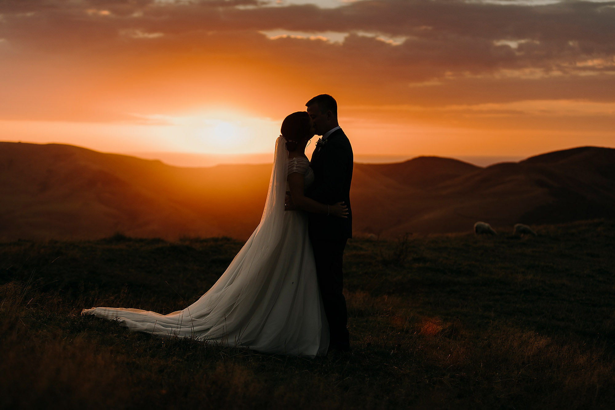 bride and groom kissing at sunset ontop of hills silhouette jonkers farm christchurch wedding photographer