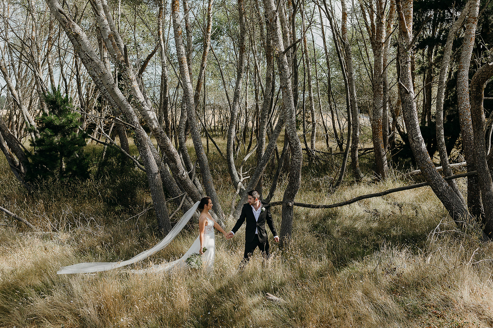 Christchurch Wedding Photographer bride and groom walking amongst trees in West Melton Christchurch Rebecca Claridge Photography