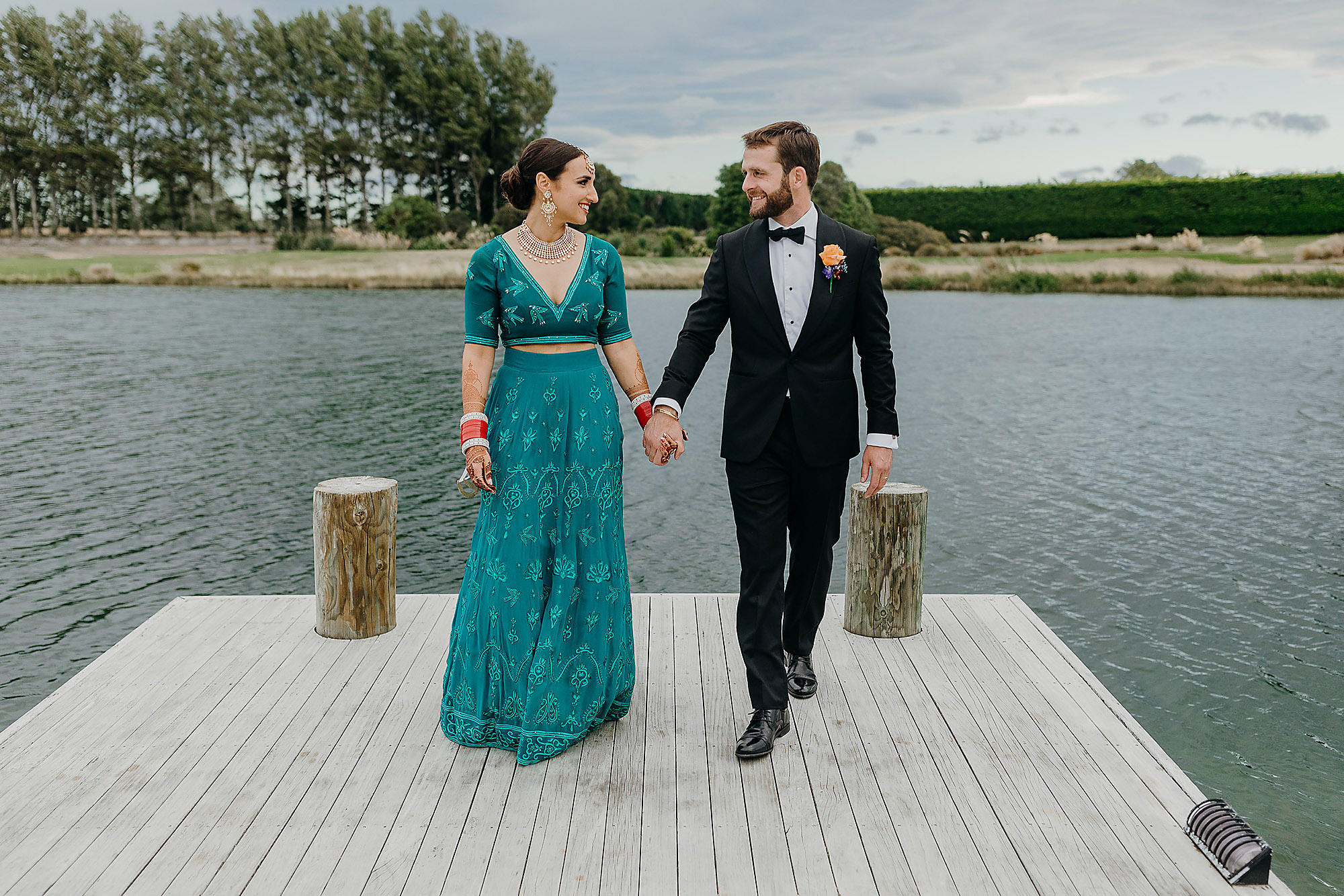 bride and groom walking together on jetty indian wedding christchurch wedding photographer