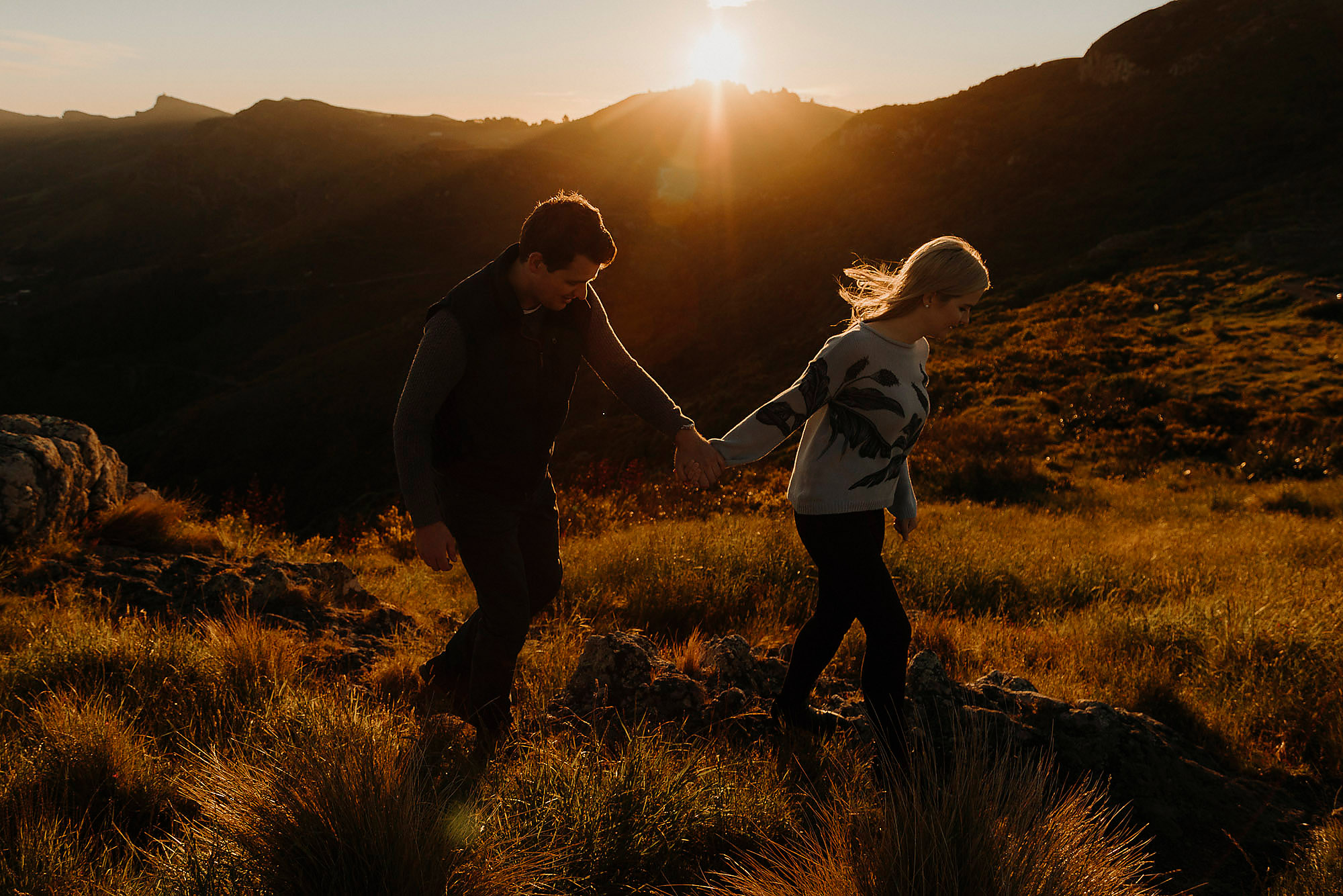 couple walking along port hills together at golden hour Engagement & Couples photographer in Christchurch