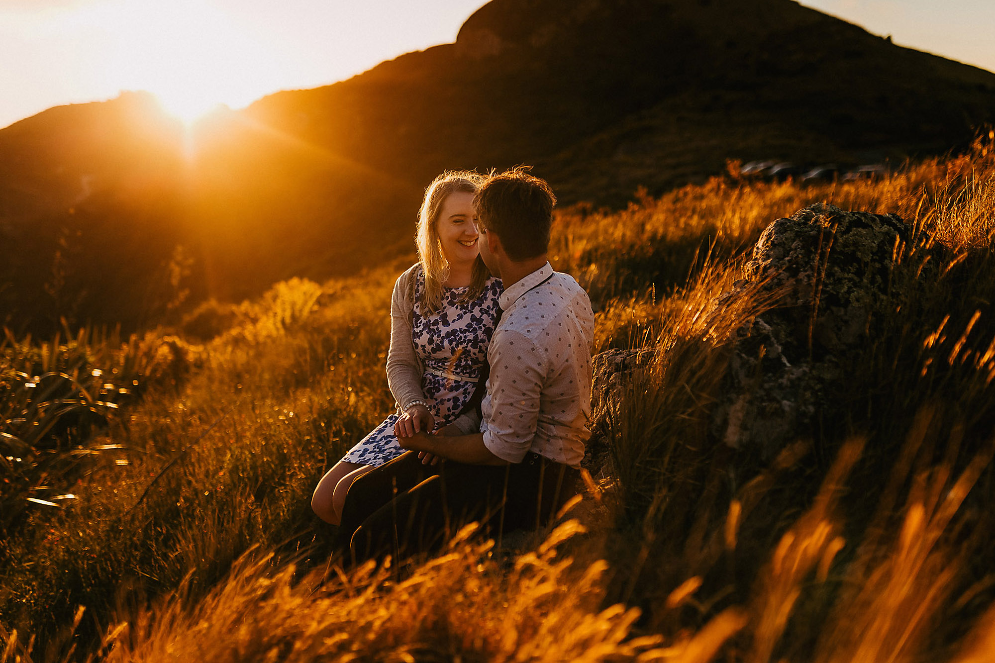 Engagement & Couples photographer in Christchurch couple smiling at each other at golden hour in the port hills