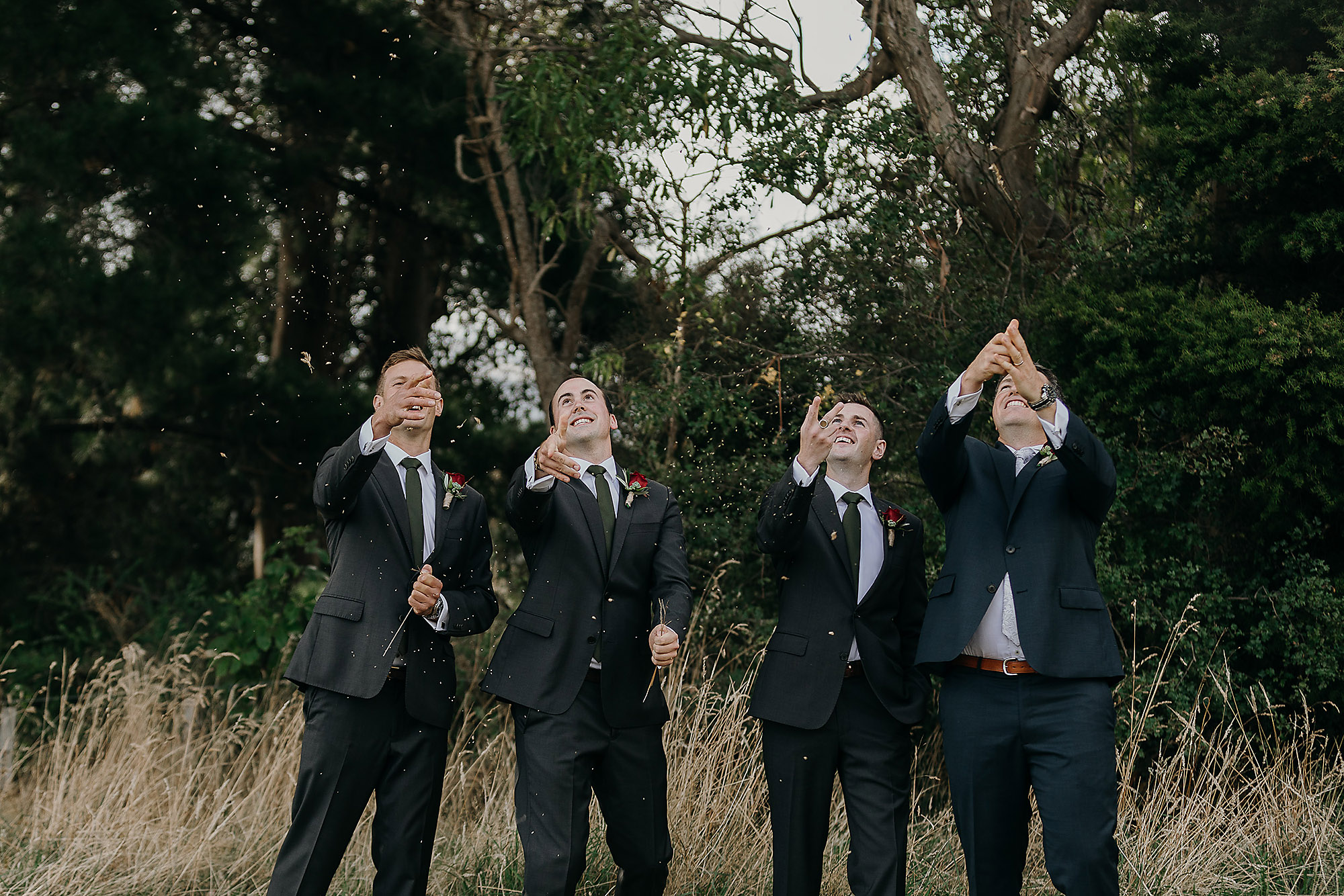 groom and groomsmen having fun with dry grass akaroa wedding christchurch wedding photographer
