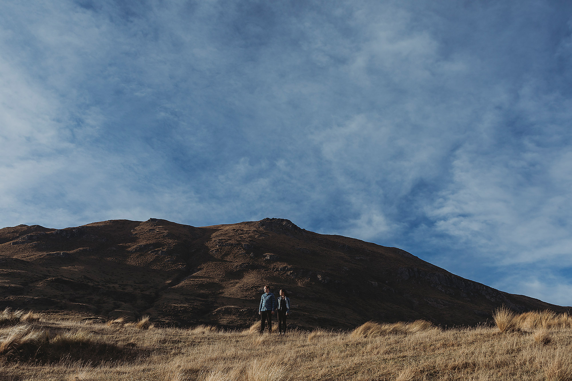 couple standing under rugged hill lake coleridge christchurch engagement photographer