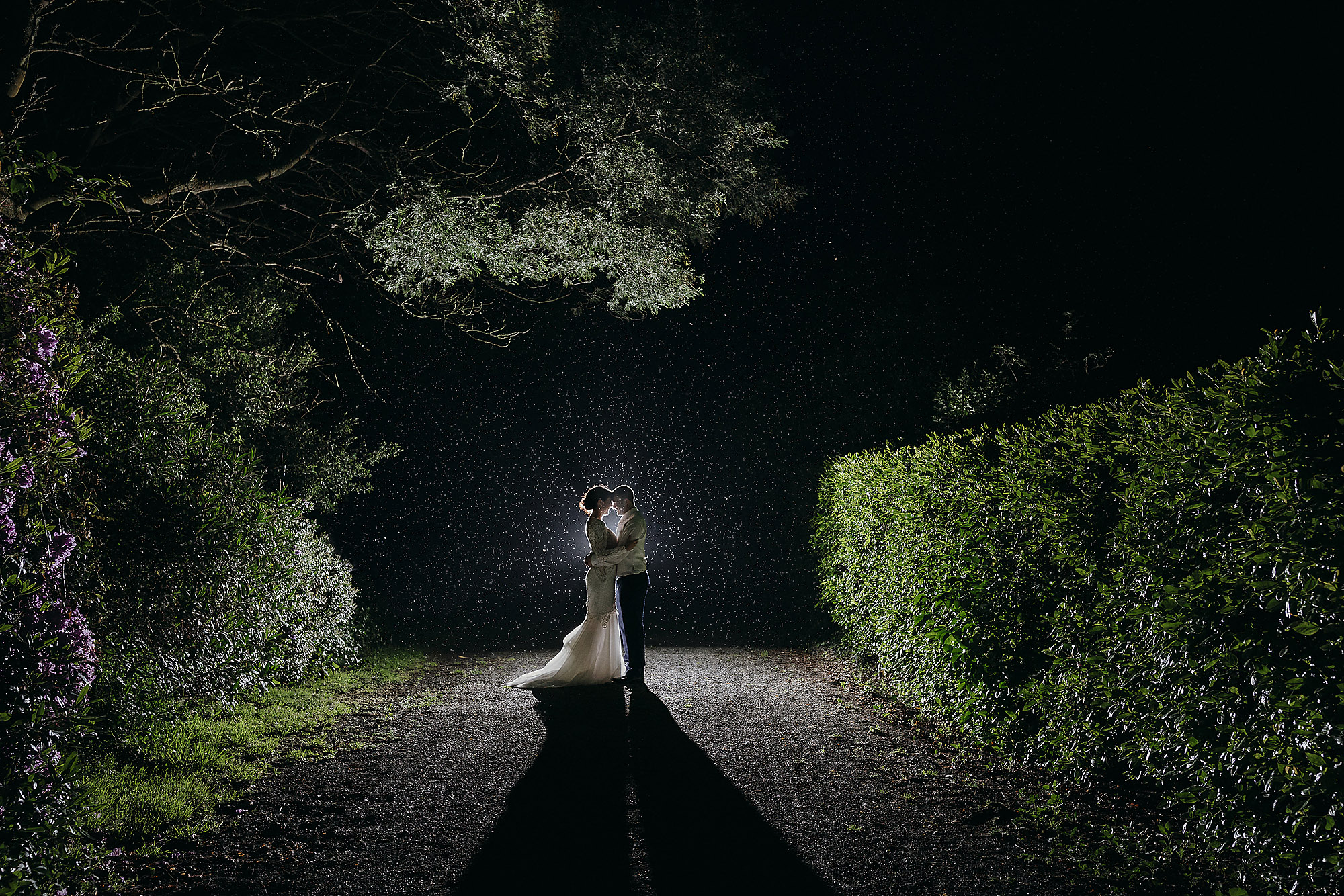 Christchurch Wedding Photographer rain wedding photo with bride and groom at night backlit in Christchurch Rebecca Claridge Photography