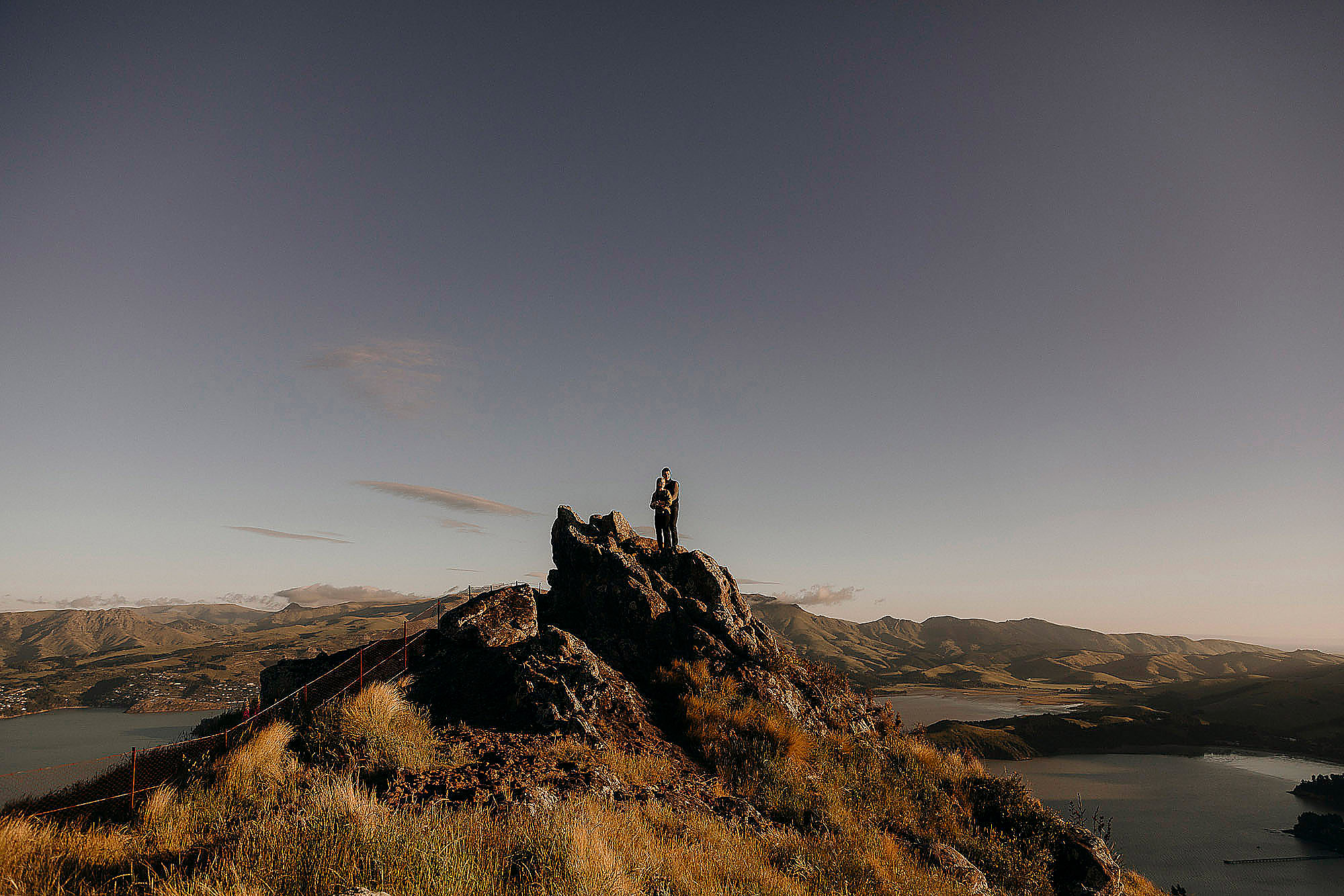 couple standing on rock together looking at view in port hills for photo session christchurch engagement photographer
