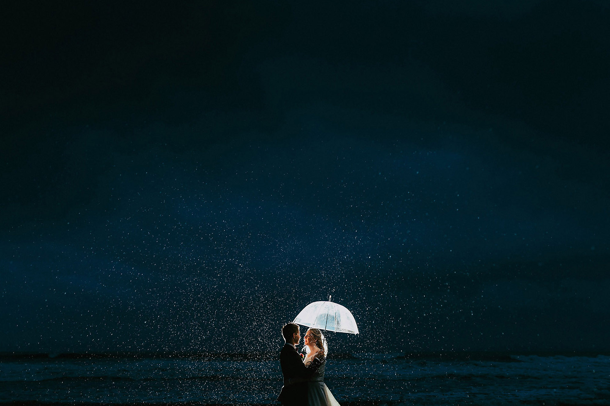 bride and groom night photo in the rain backlight at the beach south brighton christchurch wedding photographer