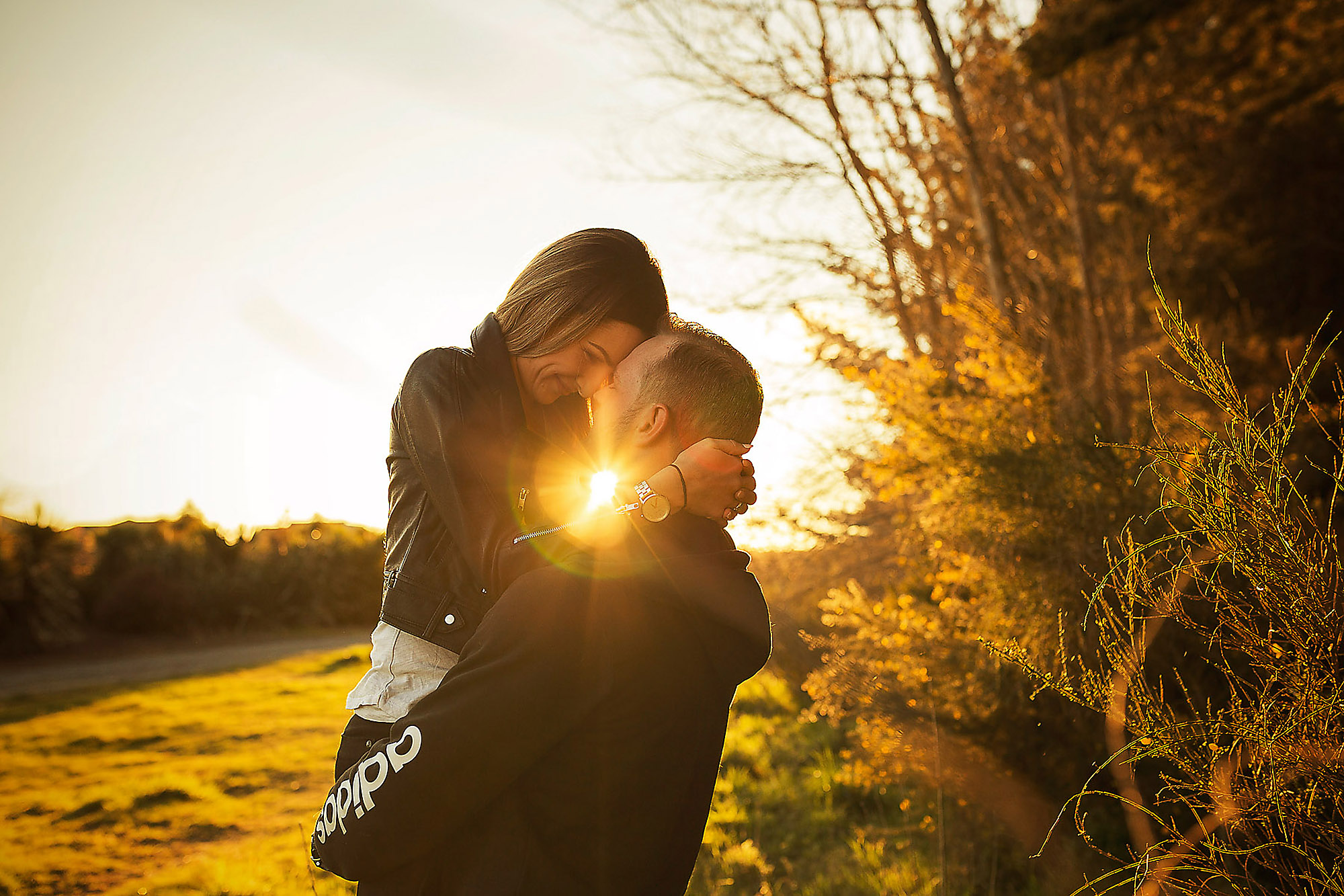 Engagement & Couples photographer in Christchurch sunset photoshoot of couple lifting girl with sunflare
