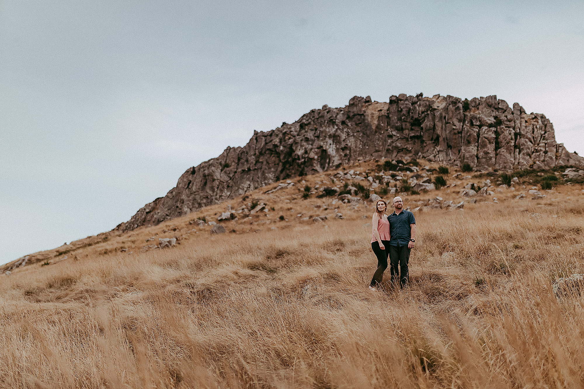 couple standing under witch hill in port hills for photo session christchurch engagement photographer